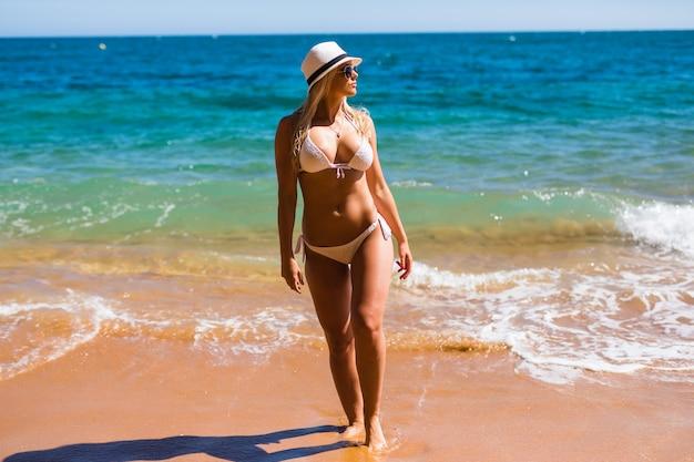 Uma garota jovem e bonita tem férias sazonais de inverno na praia em um país exótico