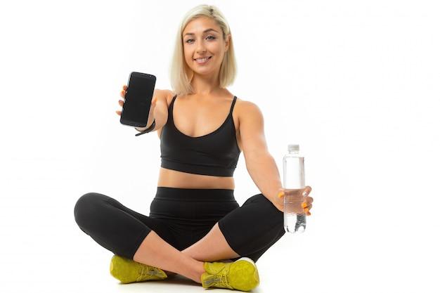 Uma garota jovem esportes com cabelos loiros e manicure brilhante em um top preto esportes e leggings detém uma garrafa de água e mostra um telefone preto.