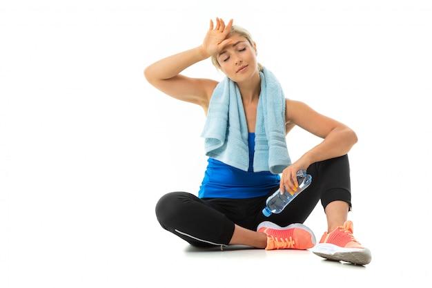 Uma garota jovem esportes com cabelos loiros em um machado preto esportes, leggings pretas e tênis brilhantes com uma toalha em volta do pescoço e uma garrafa de água cansada após o treino.