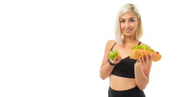 Uma garota jovem esportes com cabelos loiros em um top preto esportes e leggings pretas detém uma maçã verde e sanduíche.