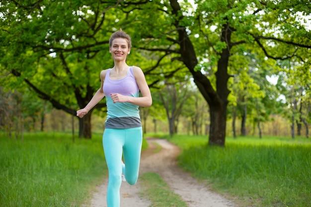 Uma garota jovem esportes correndo em uma floresta de verão verde parado. esporte e bem-estar