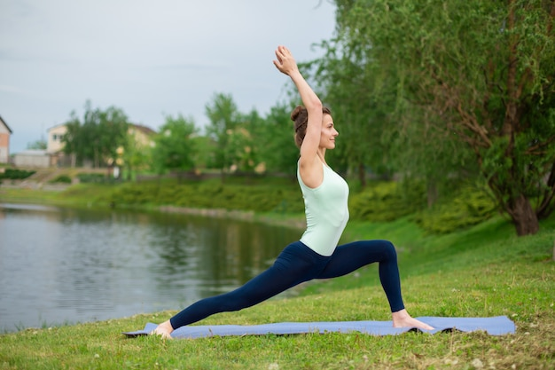 Uma garota jovem esportes pratica ioga em um gramado verde junto ao rio, postura de assans. unidade com a natureza