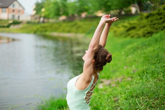 Uma garota jovem esportes pratica ioga em um gramado verde junto ao rio, postura de yoga assans. meditação e unidade com a natureza