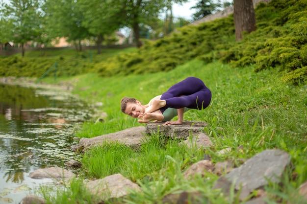 Uma garota jovem esportes pratica ioga em um gramado verde junto ao rio, postura de yoga assans.