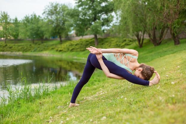 Uma garota jovem esportes pratica ioga em um gramado verde junto ao rio