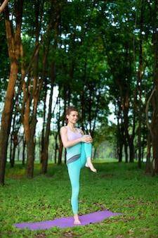 Uma garota jovem esportes pratica ioga em uma floresta de verão verde sair, postura de yoga assans. meditação e unidade com a natureza