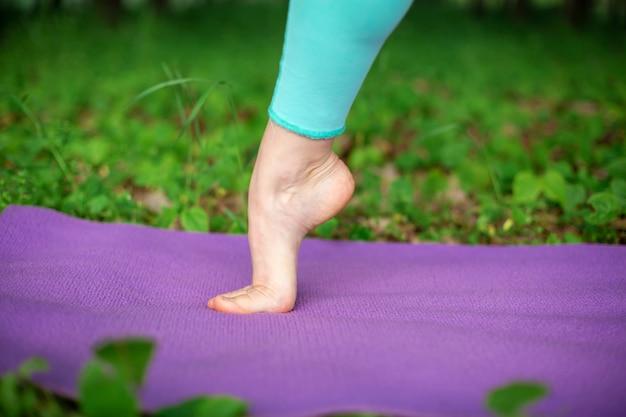 Uma garota jovem esportes pratica ioga em uma floresta de verão verde sair, postura de yoga assans