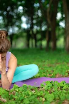 Uma garota jovem esportes pratica ioga em uma floresta de verão verde sair