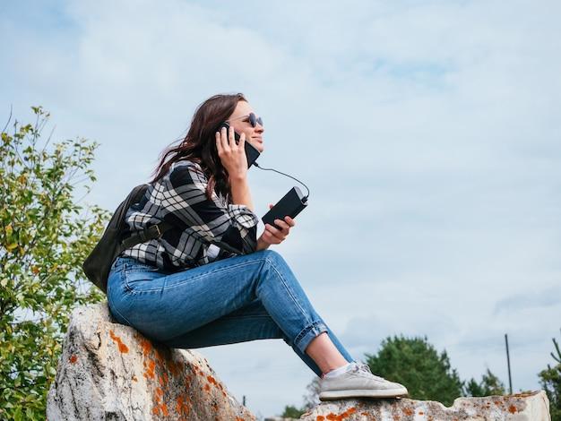 Uma garota legal em uma camisa xadrez casual, jeans e óculos está falando ao telefone conectado a um banco de energia