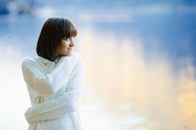 Uma garota linda em um suéter branco sorri