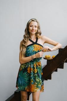 Uma garota linda em um vestido de verão com uma estampa tropical está de pé perto de uma escada de madeira. férias de verão tropical
