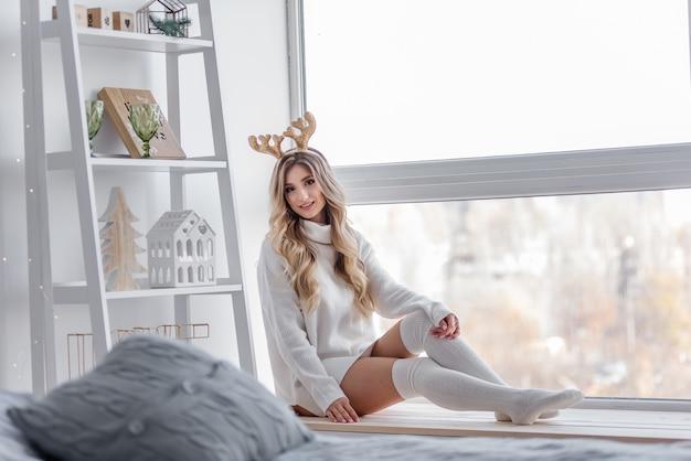 Uma garota loira com chifres de veado de natal dourados em um suéter de malha cinza, legging longa está sentada no parapeito da janela panorâmica. há uma prateleira branca com estatuetas caseiras. copiar espaço desfocado
