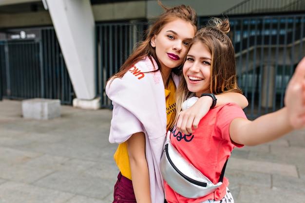 Uma garota loira deslumbrante inspirada com bolsa prateada fazendo selfie com a irmã antes de fazer compras em dia de verão