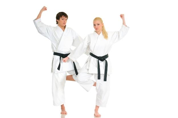 Uma garota loira e forte e o cara do caratê atrevido estão treinando em um quimono em um branco