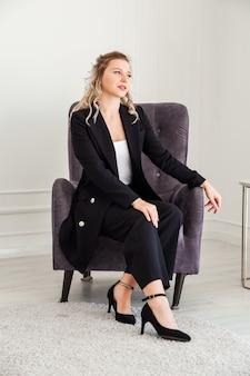 Uma garota loira em um terno preto e sapatos de salto alto se senta em uma cadeira e posa para a câmera.