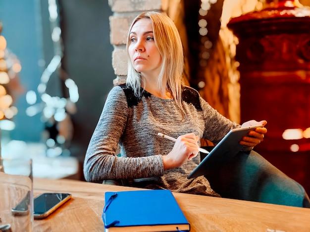 Uma garota loira está trabalhando em um café com um tablet, um telefone e um notebook nas proximidades. coworking, organização do fluxo de trabalho. conceito de negócios.