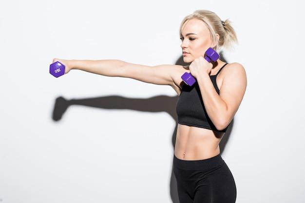 Uma garota loira musculosa e forte com halteres azuis em branco