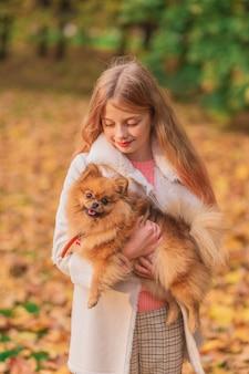 Uma garota loira segurando um spitz nos braços no parque.
