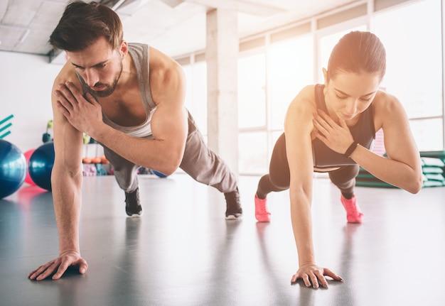 Uma garota magra e um homem forte estão em uma posição de prancha com uma das mãos e se equilibrando na outra