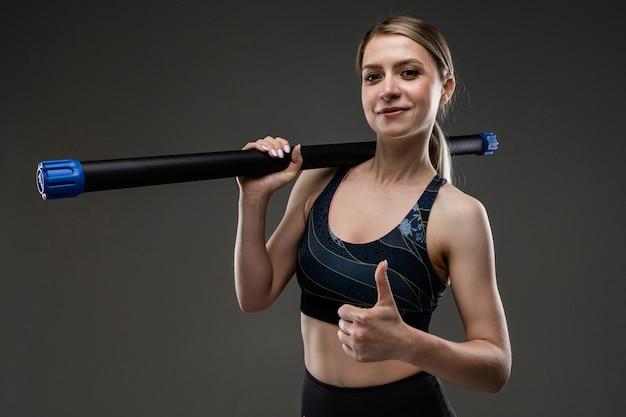 Uma garota magra em uma blusa de esportes segura uma vara de ginástica no ombro