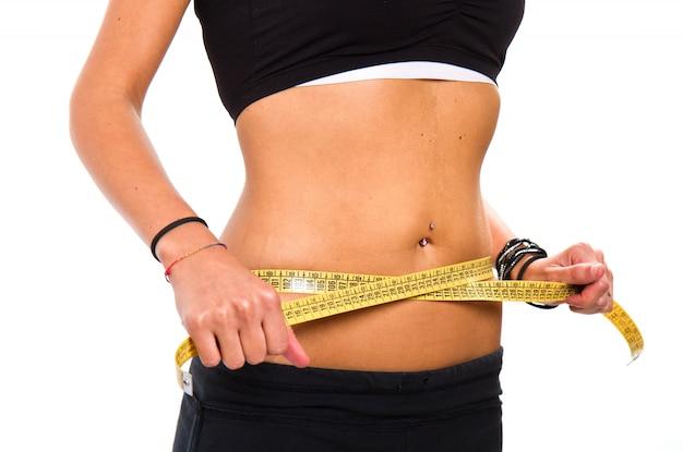 Uma garota magra medindo sua cintura