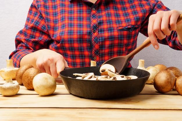 Uma garota mexendo cogumelos em uma frigideira com uma colher de pau. uma garota com uma camisa quadriculada vermelha prepara cogumelos em um fundo de madeira.