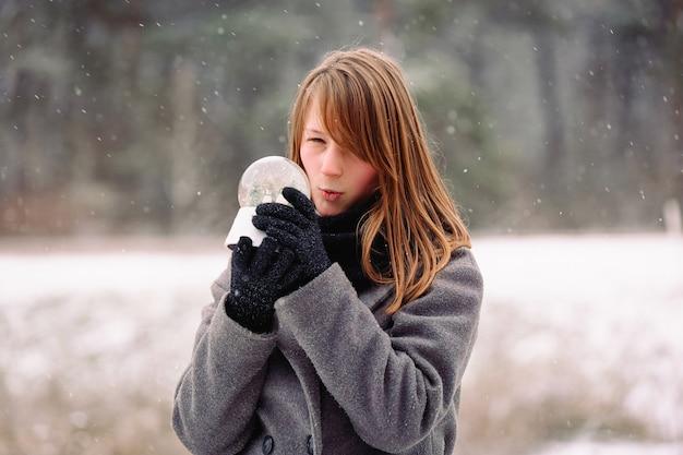 Uma garota misteriosa com um rosto surpreso examina uma bola de neve de cristal mágica. emoção energética