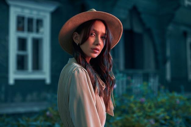 Uma garota misteriosa em um vestido e chapéu de palha fica perto de uma velha casa de madeira olhando diretamente para a câmera. sessão de fotos criativa em tons de vermelho. foto de alta qualidade