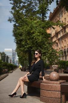 Uma garota modelo com pernas longas em um vestido preto e óculos escuros, sentada no banco e desfrutando de um sol ...