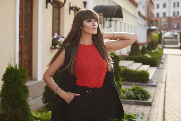 Uma garota modelo elegante com maquiagem brilhante em uma blusa vermelha em um dia ensolarado de verão. jovem mulher com roupa elegante, posando ao ar livre.