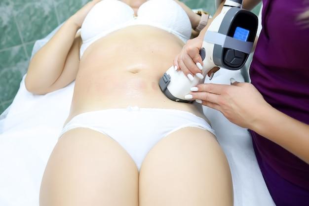 Uma garota modelo em cueca branca está na frente do mestre no procedimento de remoção de celulite a vácuo por massagem