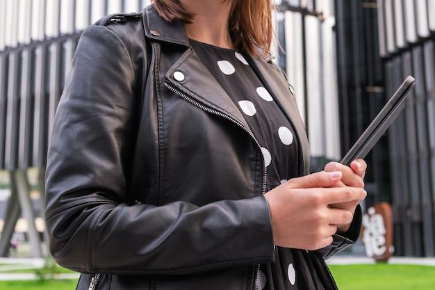 Uma garota moderna em um lindo vestido vai para uma reunião de negócios com um tablet na mão