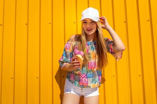 Uma garota muito jovem e hippie se divertindo ao ar livre com uma tampa branca e tomando sorvete no amarelo