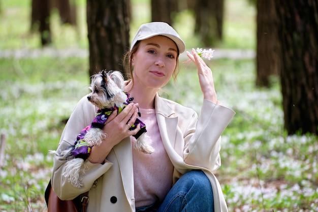 Uma garota na floresta com um cachorro e um floco de neve na mão.