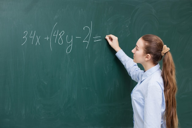 Uma garota na lousa em uma aula de matemática