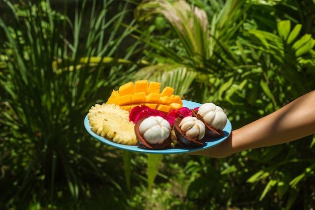 Uma garota na selva verde está segurando um prato com frutas tropicais recém-cortadas e descascadas
