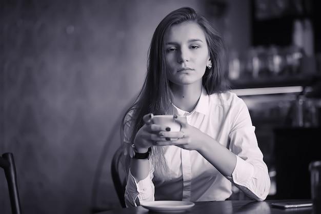 Uma garota no café está bebendo café. uma mulher está tomando café da manhã em um restaurante. café da manhã na cafeteria para a menina.