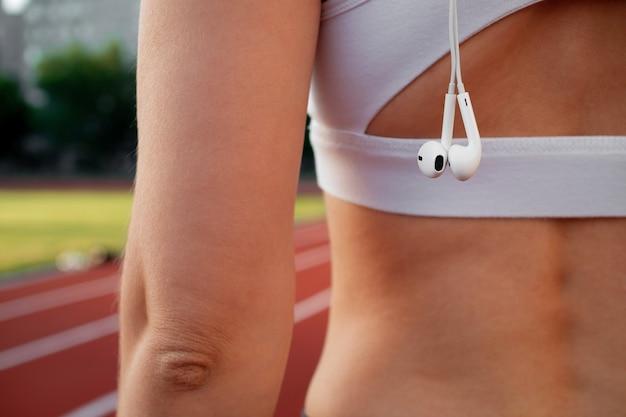 Uma garota no estádio com um fone de ouvido branco durante um treino e um close-up da maratona, vista traseira. fones de ouvido com fio no ombro. o conceito de treinamento ao ar livre