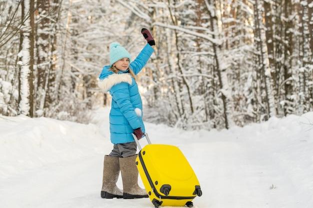 Uma garota no inverno com botas de feltro vai com uma mala em um dia gelado de neve.