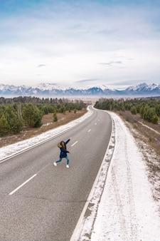 Uma garota no meio da estrada mostra montanhas nevadas