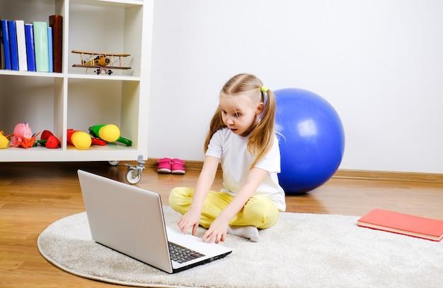 Uma garota olha para o computador. a criança está surpresa.