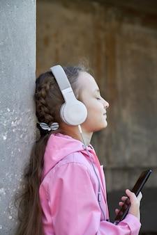 Uma garota ouvindo música em fones de ouvido contra uma parede de concreto