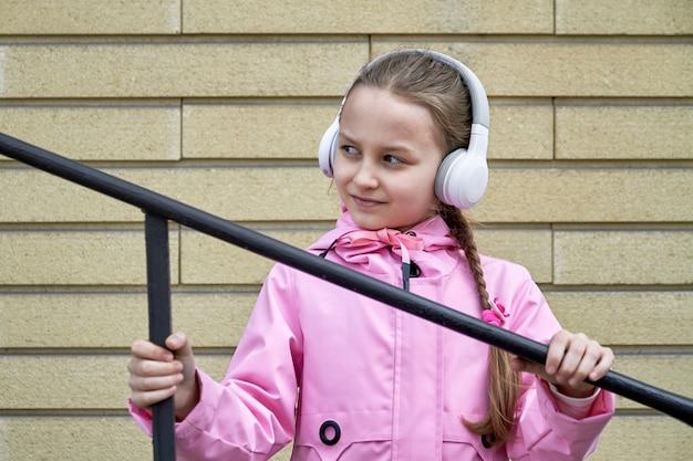 Uma garota ouvindo música em fones de ouvido contra uma parede de tijolos