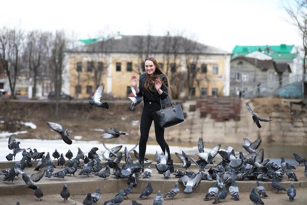 Uma garota passeando no parque e um bando de pombos
