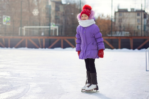 Uma garota patina em uma pista de gelo no inverno. rinque de patinação no pátio da cidade. criança aprende a andar de skate
