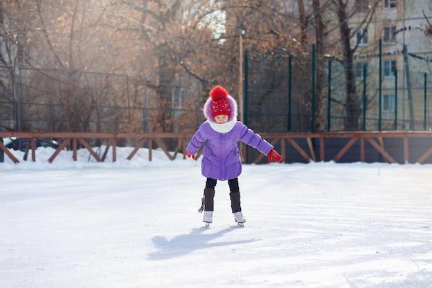 Uma garota patina em uma pista de gelo no inverno. rinque de patinação no pátio da cidade. criança aprende a andar de skate Foto Premium