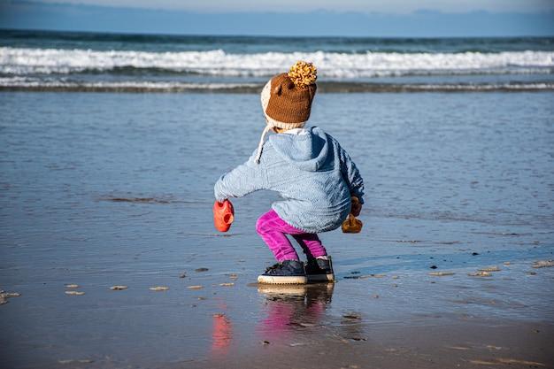 Uma garota pegando água do mar com um regador no inverno