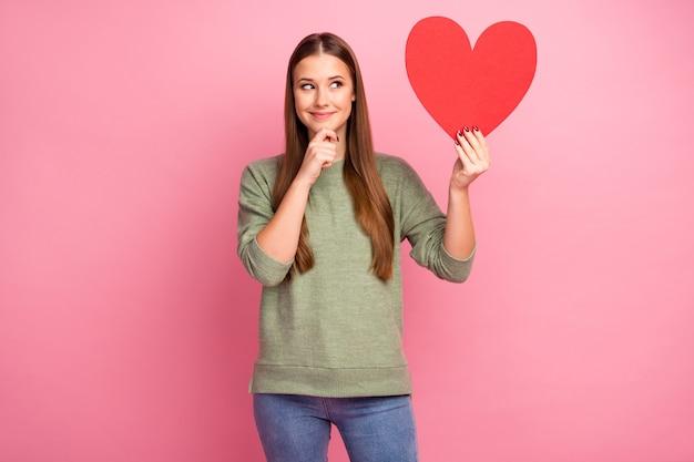 Uma garota positiva segura segurando um grande cartão de papel vermelho com um coração, pense, pareça um espaço vazio