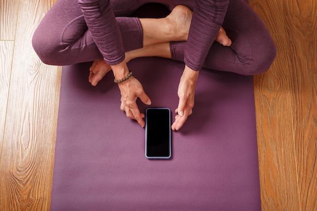 Uma garota praticando ioga e meditação em casa em um tapete lilás usando um smartphone e um aplicativo móvel