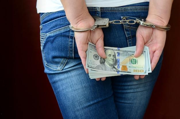 Uma garota presa com as mãos algemadas com uma enorme quantidade de notas de dólar. vista traseira